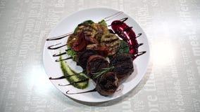 Medalhão do prato da carne no molho com vegetais fritados vídeos de arquivo