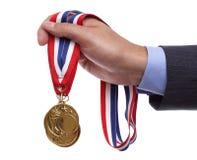 Medalha de ouro da terra arrendada do homem de negócios fotos de stock