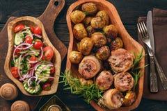 Medalions cuits au four de porc en lard avec des pommes de terre Images stock