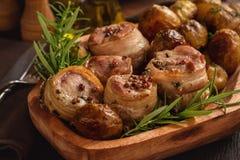 Medalions cuits au four de porc en lard avec des pommes de terre Photographie stock