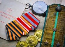 Medaljer, skuldraremmar, garnisonlock och armébok av världskrig II Royaltyfri Foto