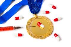 Medalla de oro con la jeringuilla y las píldoras fotos de archivo libres de regalías