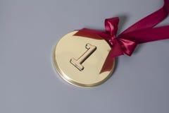 Medalla de oro del campeón con la cinta roja Imágenes de archivo libres de regalías