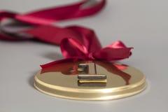Medalla de oro del campeón con la cinta roja Imagen de archivo