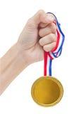Medalla de oro en mano de la mujer. Foto de archivo