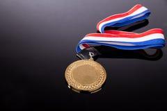 Medalla de oro genérica del evento que se divierte con la cinta roja y azul Fotos de archivo libres de regalías