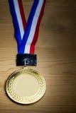 Medalla de oro genérica del evento que se divierte con la cinta roja y azul Fotografía de archivo