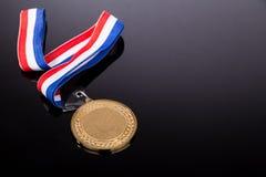 Medalla de oro genérica del evento que se divierte con la cinta roja y azul Imágenes de archivo libres de regalías