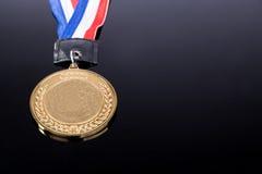 Medalla de oro genérica del evento que se divierte con la cinta roja y azul Fotografía de archivo libre de regalías