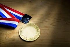 Medalla de oro genérica del evento que se divierte con la cinta roja y azul Foto de archivo libre de regalías