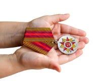 Medalla en las manos de un niño Aislado en blanco Fotografía de archivo libre de regalías