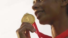 Medalla sonriente y que disfruta de la deportista feliz de la raza mixta de la victoria y de oro metrajes