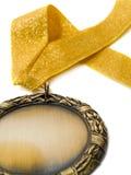Medalla y cinta de oro imagenes de archivo