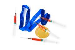 Medalla y jeringuillas de oro imagen de archivo libre de regalías
