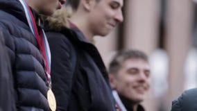 Medallas de oro de la caída de la mujer en muchachos jovenes en la calle concedido ganadores almacen de video