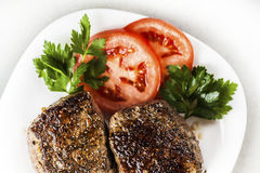 Medallion on a plate with slices of tomato Stock Photography