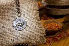Medallion with the sign of Aries and saffron. Medallion with the sign of Aries on sackcloth and saffron in a wooden spoon stock photos