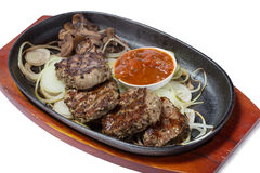 Medallions of beef with mushrooms in the frying pan. Royalty Free Stock Photography