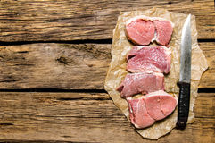 Medallions of fresh raw meat and the carving knife. Stock Photography