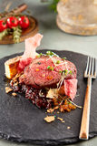 Medallions of veal. With gratin from potatoes and onion and meat sauce with fresh herbs on dark stone next to fork on background of blurry tomatoes and rosemary Royalty Free Stock Photo
