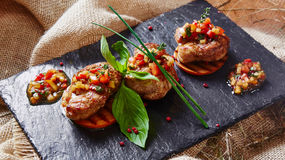 Medallions of veal. Veal medallions on slices of persimmon grill Royalty Free Stock Photo