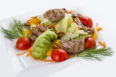 Medallions of veal with vegetables and salad. On a white plate stock image