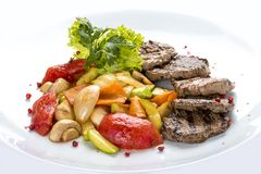 Medallions of veal with vegetables and salad. On a white plate stock photo