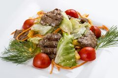 Medallions of veal with vegetables and salad. On a white plate stock photography