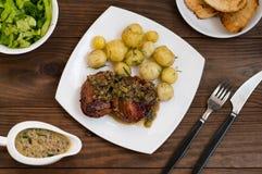 Medallones del cerdo en salsa de seta con las nuevas patatas Fuente del restaurante Vector de madera Visión superior Primer Fotografía de archivo