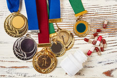 Medals and container with pills. Royalty Free Stock Images