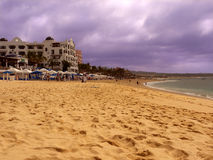 Medano Beach in Cabo Mexico. Yellow sandy beach with hotels and restaurants close by. White beach umbrellas on the beach. Dramatic sky with stormy clouds Royalty Free Stock Photo