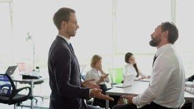Medarbetare diskuterar strategier på det stora och ljusa kontoret arkivfilmer