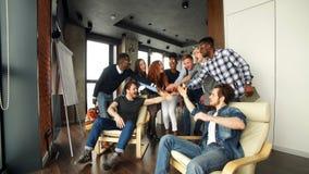Medarbetare med lyftta armar som firar lyckat möte i vindrum stock video