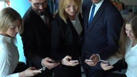 Medarbetare ser i deras smartphones tillsammans p? arbetsplats arkivfilmer