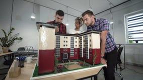 Medarbetare som diskuterar vid miniatyren av byggnad lager videofilmer