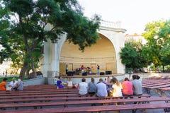 Medborgare och stadsbesökare på bänkarna på plattformen för utomhus- etapp som väntar på aftonkonserten Royaltyfri Bild