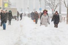 Medborgare som går vidare trottoaren i tung snöstorm i stad royaltyfri fotografi