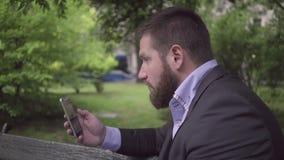 Meddelande för affärsmanhandstiltext vid smartphonen som är utomhus- arkivfilmer