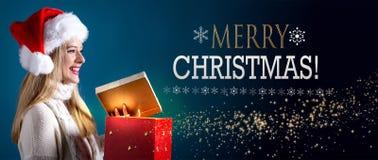 Meddelande för glad jul med kvinnan som öppnar en gåvaask arkivfoto