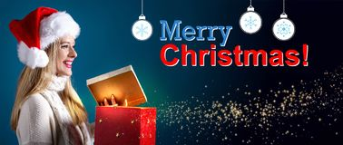 Meddelande för glad jul med kvinnan som öppnar en gåvaask arkivfoton