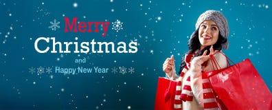 Meddelande för glad jul och för lyckligt nytt år med kvinnan som rymmer shoppingpåsar arkivbilder