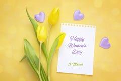 Meddelande för hälsning för dag för kvinna` s med gula tulpan på ayellowbackg arkivbild