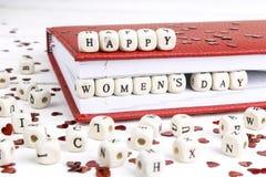 Meddelande för hälsning för dag för kvinna` som s är skriftligt i träkvarter i rött inte Arkivfoto