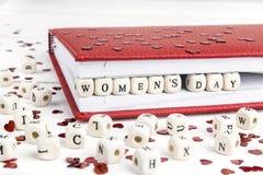 Meddelande för hälsning för dag för kvinna` som s är skriftligt i träkvarter i rött inte Royaltyfri Foto