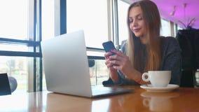 Meddelande för kvinnamaskinskrivningtext på den smarta telefonen i ett kafé Sammanträde för ung kvinna på en tabell med ett kaffe arkivfilmer