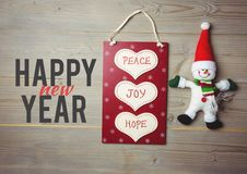 Meddelande för lycklig jul på träbakgrund med den shoppingpåsen och snögubben Royaltyfri Fotografi