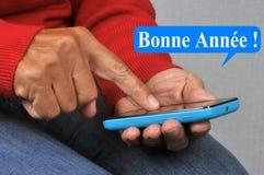 Meddelande för lyckligt nytt år som är skriftligt i fransmannen som överförs av sms arkivbild