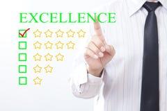 Meddelande för UTMÄRKTHET för affärsmanklickbegrepp, fem guld- stjärnor arkivfoto