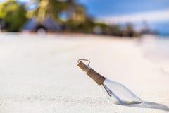 Meddelande i en flaska på en tropisk strand royaltyfria foton