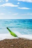 Meddelande i flaska på havsstranden Arkivfoto